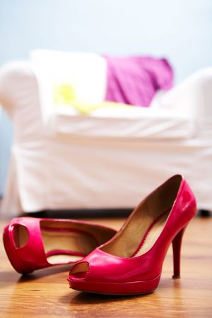 Image of red lady shoes on the floor of bedroom photo