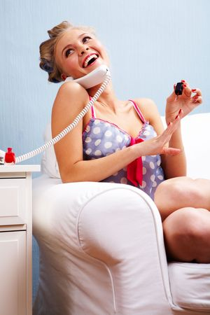 Portrait of female in curlers polishing her nails and speaking on the telephone Stock Photo - 6118872