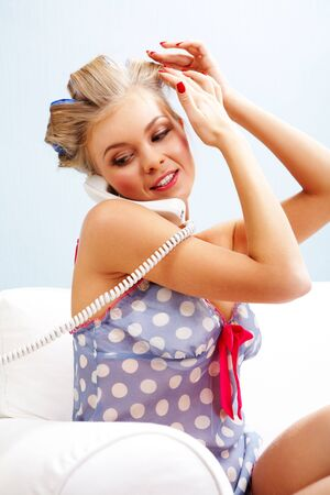 Portrait of female in curlers touching her head and speaking on the telephone at home Stock Photo - 6118888