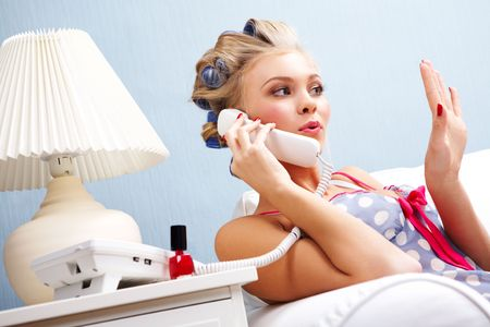 Portrait of female in curlers drying her fingernails and speaking on the telephone Stock Photo - 6118895