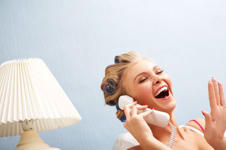 Portrait of female in curlers laughing while speaking on the telephone Stock Photo - 6118876