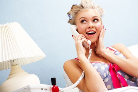 Portrait of surprised female in curlers speaking on the telephone at home Stock Photo - 6118870