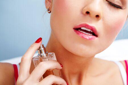 Photo of sensual woman spraying perfume onto her neck skin photo