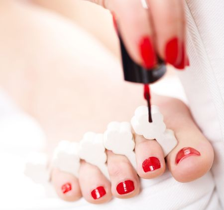 cosmetic lacquer: Close-up of female feet with red polished nails Stock Photo