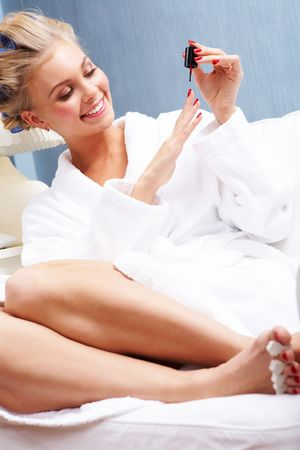Portrait of happy female in white robe polishing her nails with red lacquer Stock Photo - 6118860