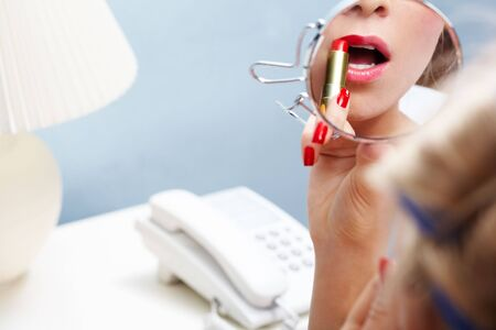 Close-up of female applying red lipstick while looking into mirror Stock Photo - 6118874