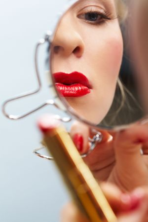 Close-up of female with red lips looking into mirror Stock Photo - 6118861