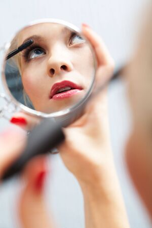 Close-up of gorgeous female looking into mirror and putting on mascara onto her eyelashes Stock Photo - 6118939