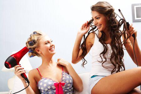 hair dryer: Foto de hembras alegres, teniendo cuidado de su pelo durante la conversaci�n Foto de archivo