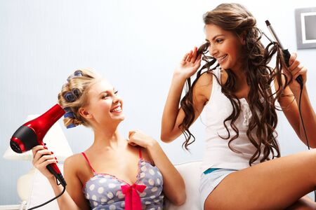 dryer: Photo of joyful females taking care of their hair while chatting