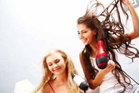 hairdryer: Photo of joyful females drying their hair and having fun Stock Photo