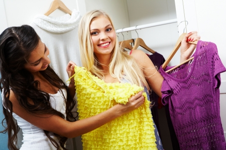 fashion clothing: Image of pretty girl trying on smart dress on her friend