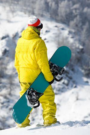 snowdrift: Rear view of snowboarder standing in snowdrift in winter