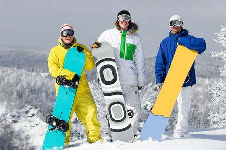 Portrait of three happy young men with snowboards looking at camera photo