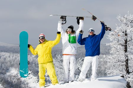 Portrait of three happy young men with snowboards raising their arms photo