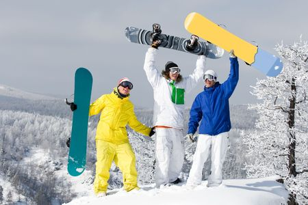Portrait of three successful snowboarders raising their arms photo