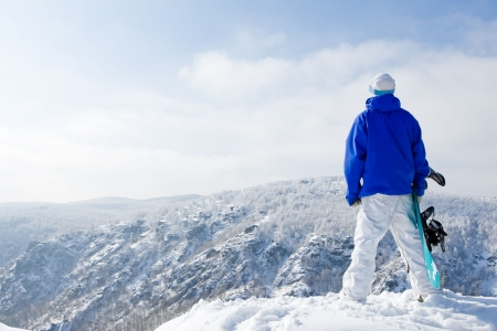 sportsmen: Rear view of sportsman with snowboard standing on top of mount Stock Photo