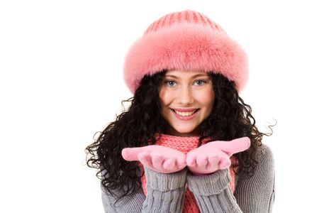 Cheerful woman in pink winter fur cap looking at camera with smile photo