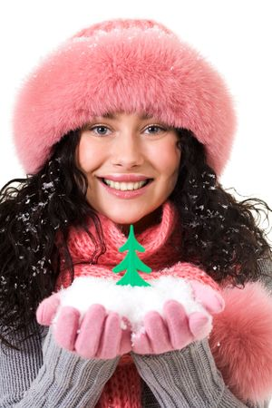 Cheerful woman in pink winter fur cap looking at camera with toy firtree on her palms photo