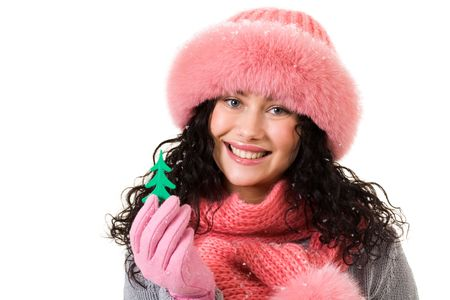 Cheerful woman in pink winter fur cap showing toy firtree in her hand photo