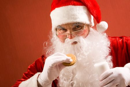 Photo of happy Santa Claus in eyeglasses looking at camera while drinking milk with bisquit Stock Photo - 6118996