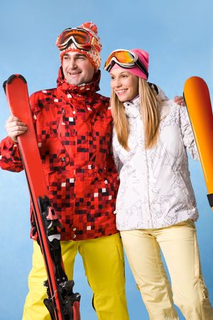 Portrait of happy couple with skis in hands looking aside with smiles photo