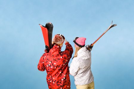 Back view of sporty couple pointing at something over blue background photo