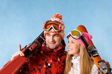 Portrait of happy couple holding skis and communicating with each other photo