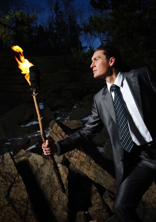 torch light: Image of elegant man holding burning stick while moving in darkness