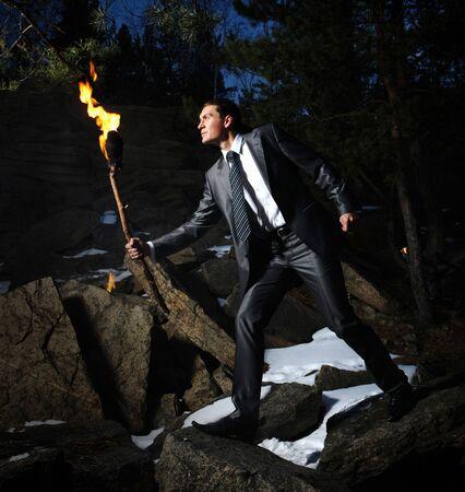 Image of elegant man holding burning stick while moving in darkness photo