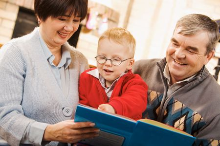 Portrait of attentive boy looking at page of book while reading it with his grandparents Stock Photo - 6131073
