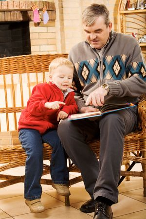Portrait of attentive boy looking at page of book while reading it with his grandfather photo