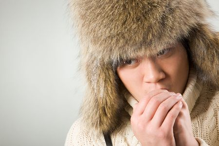 Portrait of cold man in fur hat and knitted sweater warming up his hands photo