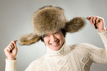 Portrait of happy man in warm fur hat and white sweater having fun photo