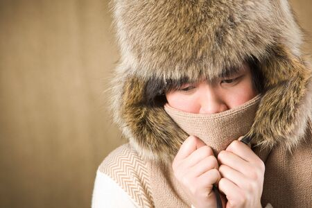 Portrait of cold man in fur hat and knitted scarf warming up photo