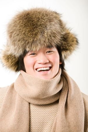 Portrait of happy man in warm fur hat and white sweater laughing photo