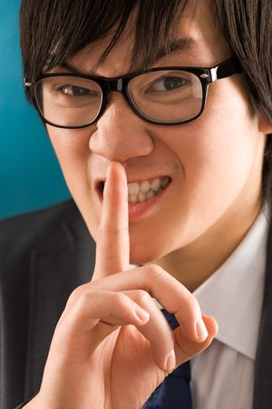 hushed: Portrait of young businessman with the finger near mouth