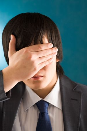 Portrait of young businessman hiding his face by hand photo