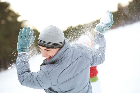 fling: Image of attractive young man laughing while under snowball bombing