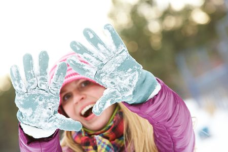 flurry: Photo of cute girl showing her gloved hands covered with snow  Stock Photo