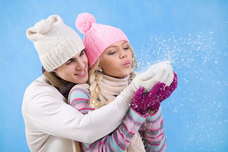 Portrait of happy young couple in warm clothes blowing snow off their palms  photo
