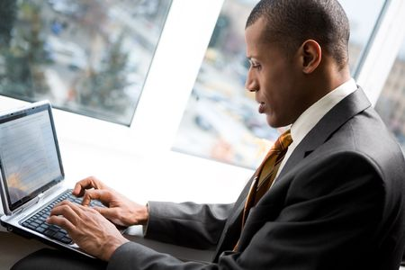 african american: Photo of handsome employee working in office with laptop in front