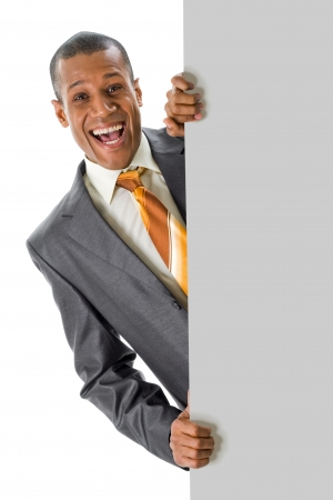 riendo: Imagen de hombre de negocios alegre peeping fuera de cartel en blanco con su anuncio