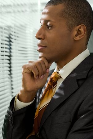 Serious businessman looking through venetian blind in office photo