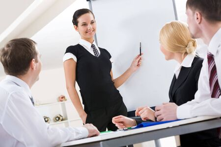 successful female standing by whiteboard while explaining her idea to colleagues Stock Photo - 6614324