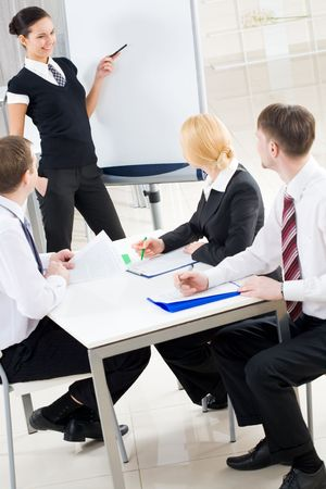 Image of several listeners looking attentively at young consultant pointing at board Stock Photo - 6614326