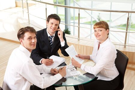 successful co-workers gathered around table and looking at camera during meeting photo