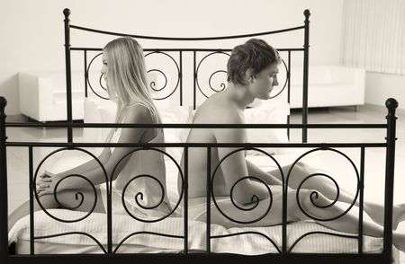 man and woman sitting on bed with sad expression photo