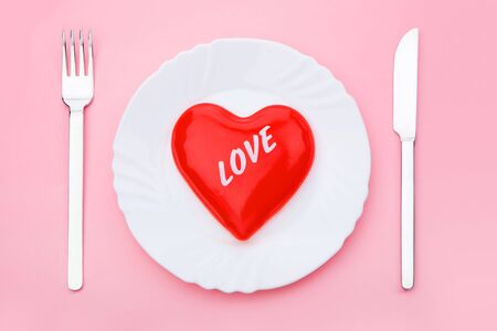 Image red heart on plate with spoon and fork near by photo
