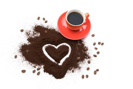Photo of cup of coffee with shape of heart drawn in ground coffee near by photo